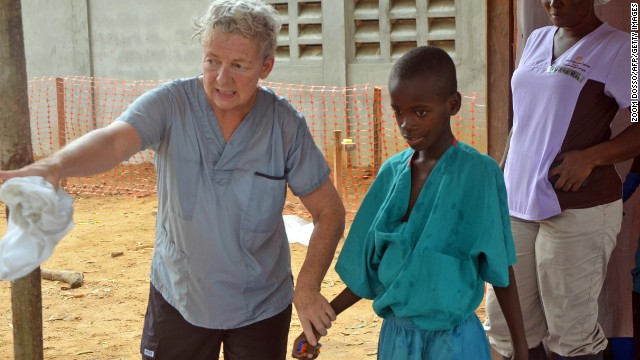 A 10-year-old boy whose mother was killed by the Ebola virus walks with a doctor from the aid organization Samaritan's Purse after being taken out of quarantine Thursday, July 24, in Monrovia.