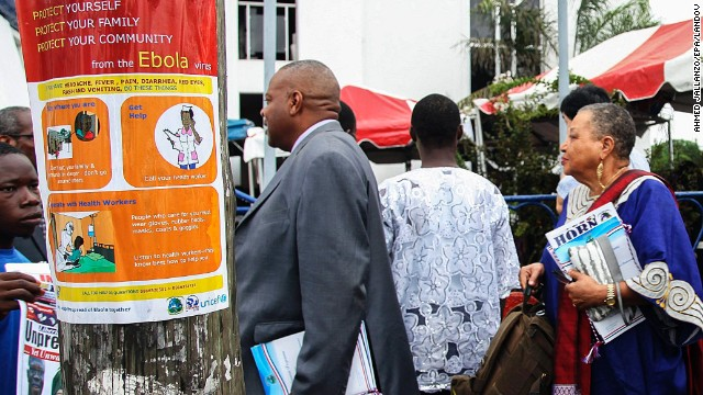 Liberian President Ellen Johnson Sirleaf, right, walks past an Ebola sensitization poster in downtown Monrovia as Liberia marked the 167th anniversary of its independence Saturday, July 26. The Liberian government dedicated the anniversary to fighting the deadly disease.