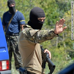 A serviceman of Ukrainian volunteer battalions of territorial defence Lugansk-1 checks passing cars at their checkpoint near the eastern Ukrainian city of Lysychansk on July 28, 2014.