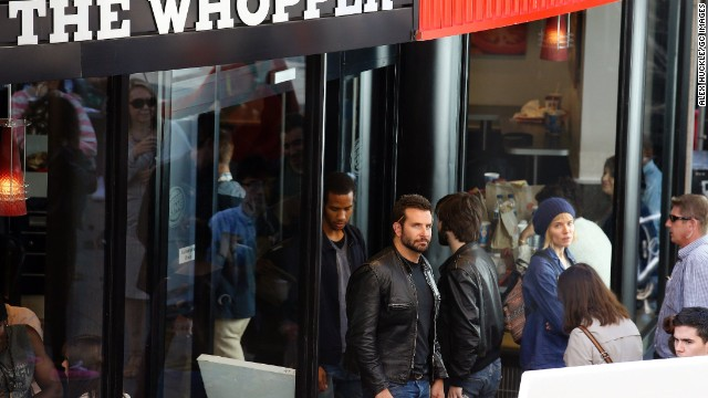 Bradley Cooper wasn't just stopping by a London Burger King for a Whopper run on July 29. He was actually doing work -- and in more ways than one. <a href='http://www.eonline.com/news/564126/why-is-bradley-cooper-working-at-burger-king' target='_blank'>According to E! News</a>, the Oscar nominee got behind the grill and learned how to flip burgers for a role in an upcoming movie.