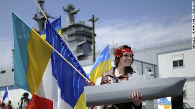 A woman holds a French and Ukrainian flag and a model of a boat as she demonstrates in front of the warship in Saint-Nazaire.