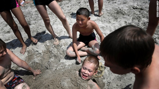 North Korean Kim Sun Gun, 12, smiles as Russian student Konstantin Kostya, 10, is buried in the sand. The camp was opened in the 1980s to foster ties with other communist-bloc countries.
