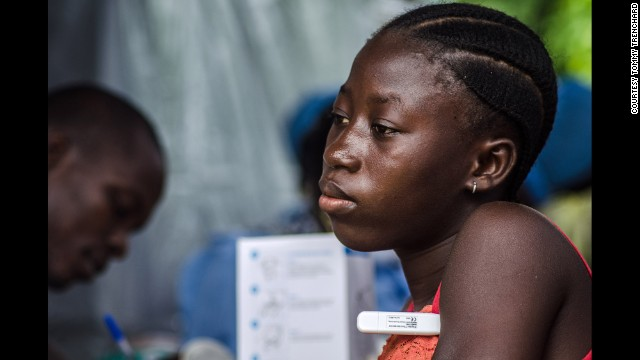 A woman has her temperature taken at a screening checkpoint on the road out of Kenema, Sierra Leone, on July 9.