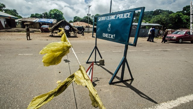 Police block a road outside the town of Kenema, Sierra Leone, on Wednesday, July 9, in order to stop motorists for a body temperature check.