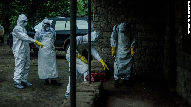 Red Cross volunteers prepare to enter a house where an Ebola victim died in Pendembu, Sierra Leone, on Friday, July 18.