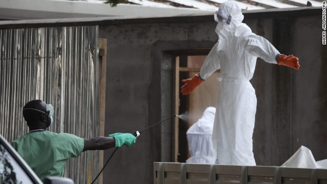 Nurses wearing protective clothing are sprayed with disinfectant Friday, August 1, in Monrovia after they prepared the bodies of Ebola victims for burial.