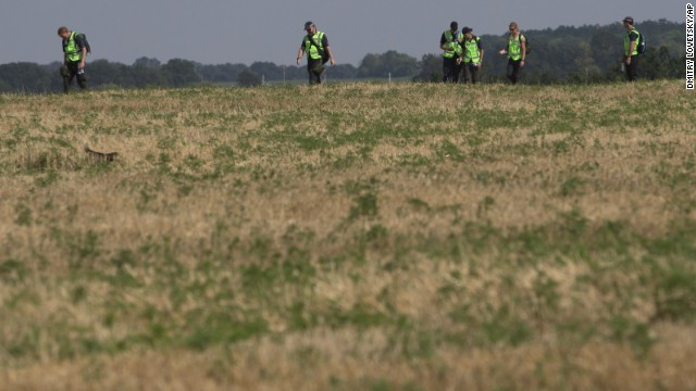 Australian and Dutch experts examine the area of the Malaysia Airlines Flight 17 plane crash on August 3, near the village of Rossipne, in the Donetsk region of eastern Ukraine.