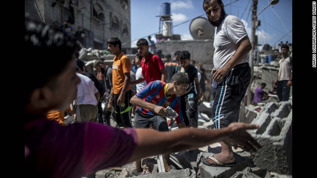 Palestinians remove rubble from a house hit by an airstrike in the al-Shati refugee camp in Gaza City on August 4.