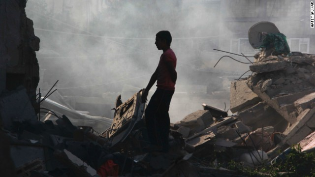 A Palestinian boy looks for belongings after an airstrike in Rafah on Saturday, August 2.
