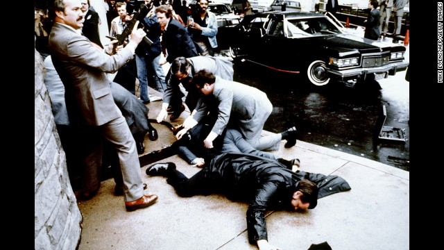 Police and Secret Service agents react during the Reagan assassination attempt, which took place March 30, 1981, after a conference outside the Hilton Hotel in Washington. Lying on the ground in front is wounded police officer Thomas Delahanty. Brady is behind him, also lying face down.