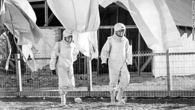 "A virus begins killing people in New Mexico after a satellite falls to Earth in the 1971 movie ""The Andromeda Strain."" Scientists in an isolated lab study the virus, which dangerously mutates before becoming benign."