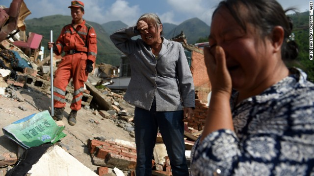Women react as the body of a relative is found in the collapsed rubble of a home in Longtoushan on August 5.