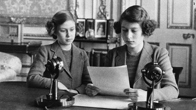 A 14-year-old Princess Elizabeth, right, sits next to her sister for a radio broadcast on October 13, 1940. On the broadcast, her first, she said that England's children were full of cheerfulness and courage.