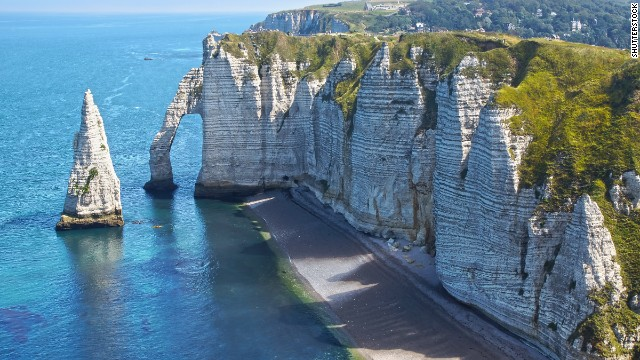 Natural arches have emerged from the chalky cliffs of Etretat, France, a scene that inspired Claude Monet and other impressionists. A wide beach fronts the resort town beyond this dramatic formation.