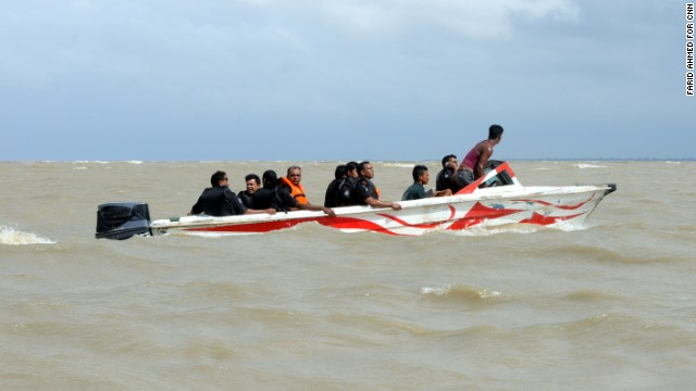 Rescuers search in vain for the capsized boat.