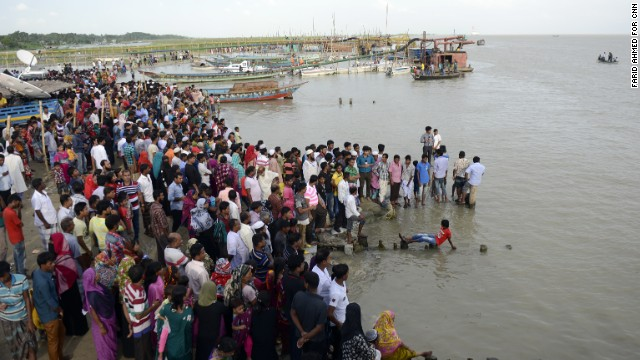 People wait at Mawa station on the bank of Padrelativma river for news of their missing relatives Tuesday.