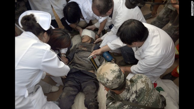 Survivor Xiong Zhengfen, 88, is treated by medical personnel on Tuesday, August 5, after being buried under rubble for 50 hours in Ludian County.