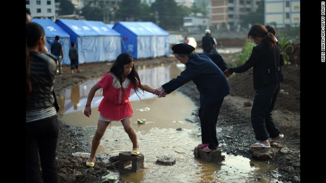 An elderly woman gets help crossing a small creek near tents set up for earthquake survivors in Longtoushan on August 6.