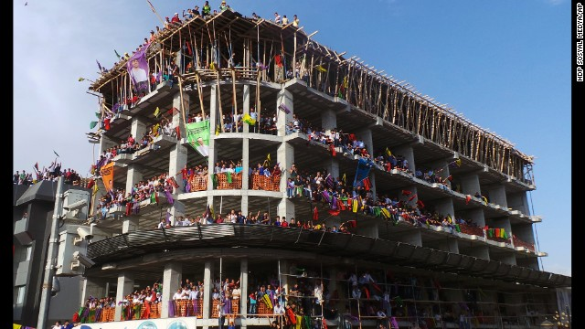 People listen to presidential candidate Selahattin Demirtas, a member of Turkey's main pro-Kurdish party, from an unfinished building as he addresses his supporters in Van, Turkey, on Tuesday, August 5.