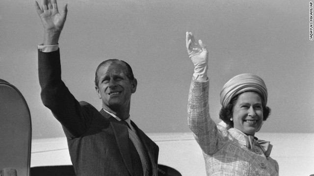 Queen Elizabeth II and Prince Philip wave from a plane ramp shortly before taking off from Tokyo in May 1975.