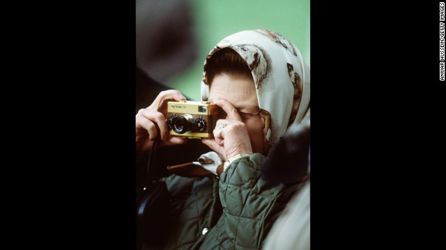 The Queen, a keen photographer, snaps a photo with a Leica camera at the Windsor Horse Show in 1978.