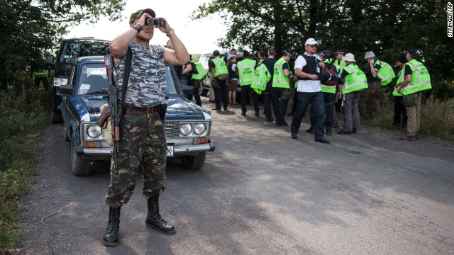 A pro-Russian separatist guards a road as Australian, Malaysian and Dutch investigators prepare to examine the crash site of Malaysia Airlines Flight 17 near the village of Rossipne, Ukraine, on August 5. U.S. and Ukrainian officials allege that a Russian-made missile shot down the plane from rebel-held territory, killing all 298 people on board. Russia and the rebel fighters deny involvement.