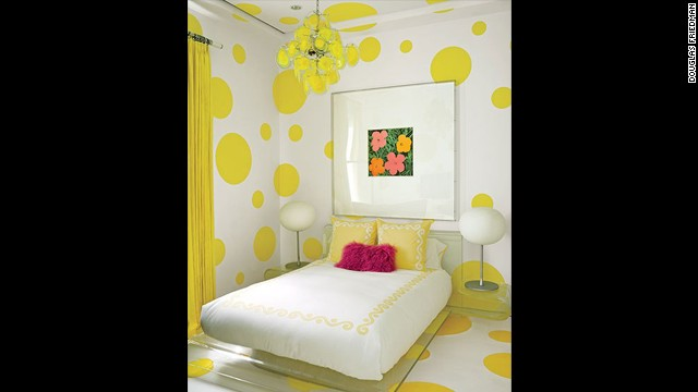 "A Warhol ""Flowers"" work hangs in a guest room that's decked out in a dotted wall treatment devised by Martyn Lawrence Bullard and painted in a Benjamin Moore yellow; the vintage chandelier is by Vistosi, the bedding is by Leontine Linens, and the felt rug is by Anthony Monaco. See more images at <a href='http://www.architecturaldigest.com/celebrity-homes/2014/dee-and-tommy-hilfiger-florida-beach-house-slideshow?mbid=synd_cnn' target='_blank'>ArchitecturalDigest.com</a>"