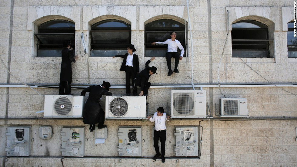 Ultra-Orthodox Jewish boys climb down a wall near the scene of what police described as a terror attack Monday, August 4, in Jerusalem. Police said they shot and killed the Palestinian driver of a construction vehicle <a href='http://www.cnn.com/2014/08/04/world/mideast-crisis/index.html'>after it overturned a passenger bus,</a> killing a pedestrian and injuring the bus driver. There were no passengers on the bus during the incident, which appeared to be a backlash against Israel's ground operation in Gaza. Israel <a href='http://www.cnn.com/2014/07/18/world/gallery/israel-gaza/index.html'>launched a ground operation in Gaza</a> on July 17, after a 10-day campaign of airstrikes had failed to halt relentless Hamas rocket fire on Israeli cities.
