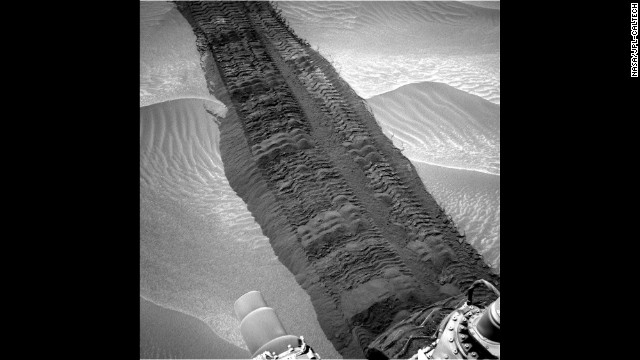 "Wheel tracks from the Mars rover Curiosity are seen on the sandy floor of a lowland area dubbed ""Hidden Valley"" in this image taken Monday, August 4. Curiosity set off from Earth in November 2011 and landed nearly nine months later -- 99 million miles away."
