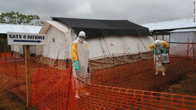 At MSF's main treatment center for Ebola patients in Kailuhun, workers dressed in protective suits spray the entrance area with chlorine.