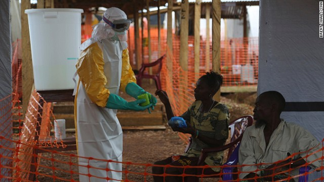 A health worker gives food to patients confirmed to have Ebola. At Kailuhun, 70% of the patients will die. Those who survive may face stigma from their communities.