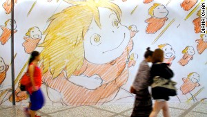 Visitors at a Studio Ghibli exhibit in Hong Kong walk by a wall of artwork.