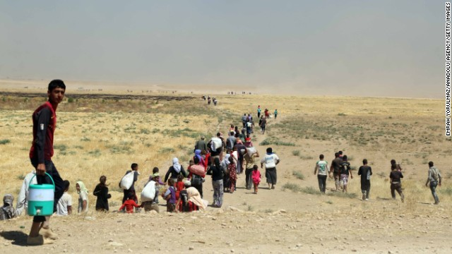 Thousands of Yazidis are escorted to safety by Kurdish Peshmerga forces and a People's Protection Unit in Mosul, Iraq, on August 9.