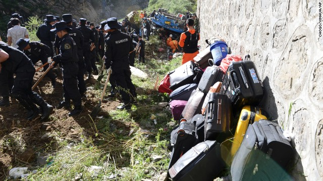 Luggage from the bus is piled against a wall as workers work near the overturned vehicle.
