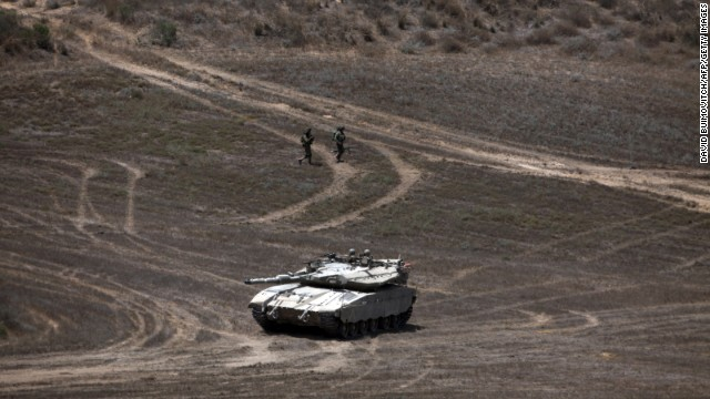 Israeli soldiers walk past a Merkava tank as