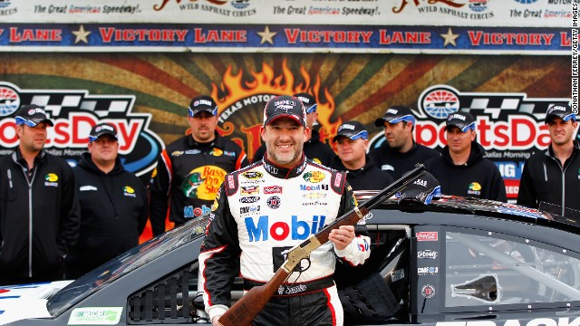 Stewart poses with a rifle given as a pole award after qualifying for pole position for the NASCAR Sprint Cup Series Duck Commander 500 at Texas Motor Speedway on April 5 in Fort Worth, Texas.