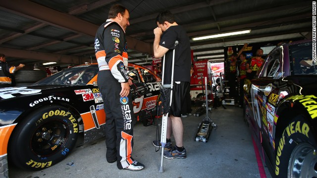 Driver Ryan Newman talks with team owner and injured driver Tony Stewart, on crutches, in the garage during practice for the NASCAR Sprint Cup Series AAA 400 at Dover International Speedway on September 28, 2013, in Dover, Delaware. Stewart broke his leg on August 5, 2013, during a race at the Southern Iowa Speedway in Oskaloosa, Iowa.