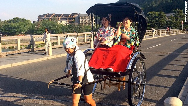 Kimono-clad Japanese tourists take a rickshaw ride over Arashiyama's Togetsukyo Bridge (Moon Crossing Bridge).