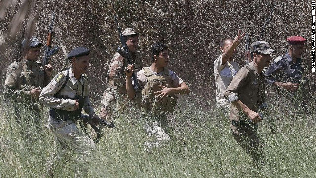 Iraqi soldiers fan out into a field in Jurf al-Sakhar on August 10 after they reportedly pushed back Islamic jihadist fighters from the area.