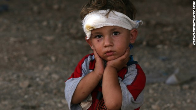 An Iraqi Yazidi child, whose family fled their home a week ago when ISIS militants attacked their town, looks on at a makeshift shelter August 10 in Dohuk, which is in Iraq's autonomous Kurdistan region.