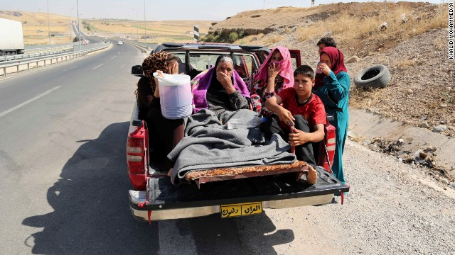 Displaced Iraqis ride on a truck on a mountain road near the Turkish-Iraq border, outside Dahuk, on August 9.
