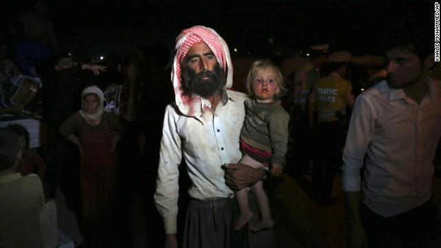 Displaced Iraqis of the Yazidi faith cross the Syria-Iraq border on Sunday, August 10.