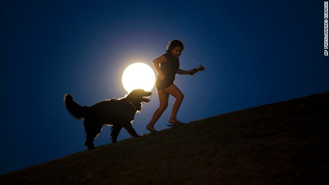 "AUGUST 10 - MADRID, SPAIN: A girl plays with a dog as a <a href='http://cnn.com/2014/08/10/world/gallery/supermoon-0810/index.html'>""supermoon"" </a>rises on August 10. The phenomenon occurs when the moon becomes full on the same day as its perigee -- the point in the moon's orbit when it is closest to Earth. This is the <a href='http://www.cnn.com/2014/07/12/world/gallery/supermoon-2014/index.html'>second one to appear in the current season. </a>"