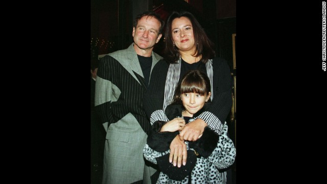 "Williams and his wife, Marsha, pose for photographers with their daughter, Zelda, as they arrive at the premiere of the film ""Patch Adams"" in December 1998 in New York City."