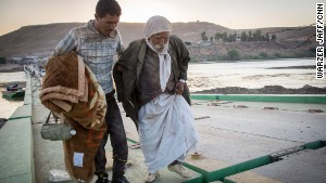 Yazidi men cross a bridge to safety in Iraqi Kurdistan.