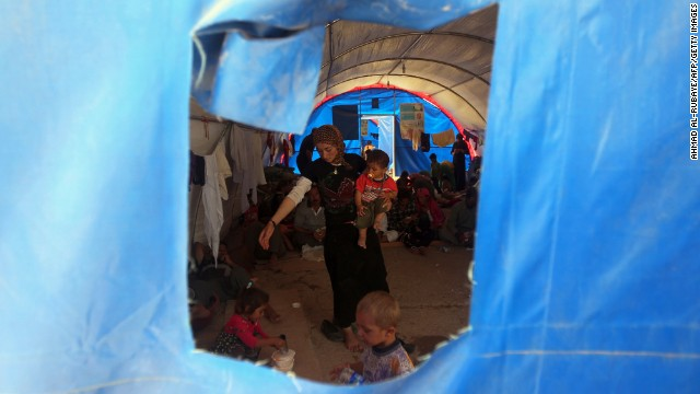 A Yazidi woman and children take shelter inside a tent at the Bajid Kandala camp on August 13.