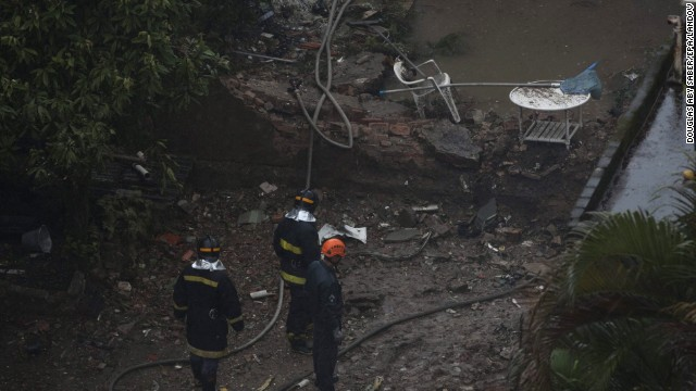 Emergency workers inspect damaged buildings where the aircraft crashed. The plane crashed into a gymnasium and two homes.