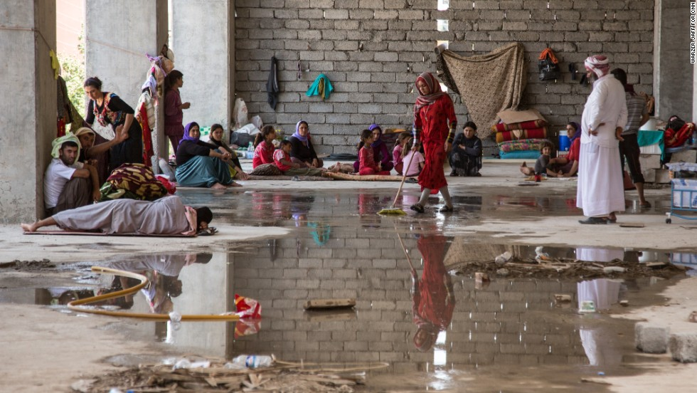 A Yazidi family from Sinjar cleans a spot for themselves in a derelict building that houses more than a thousand other refugees on Thursday, August 14, in Zakho, Iraq.