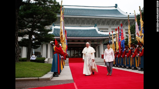 Pope Francis walks with South Korean President Park Geun-hye before a welcoming ceremony at the presidential Blue House in Seoul on August 14.