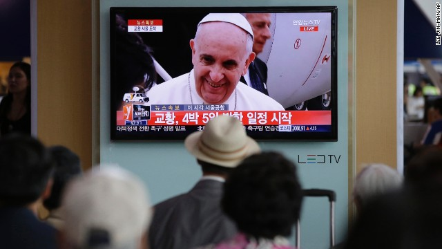 People watch Pope Francis' arrival on a television at the Seoul Railway Station.